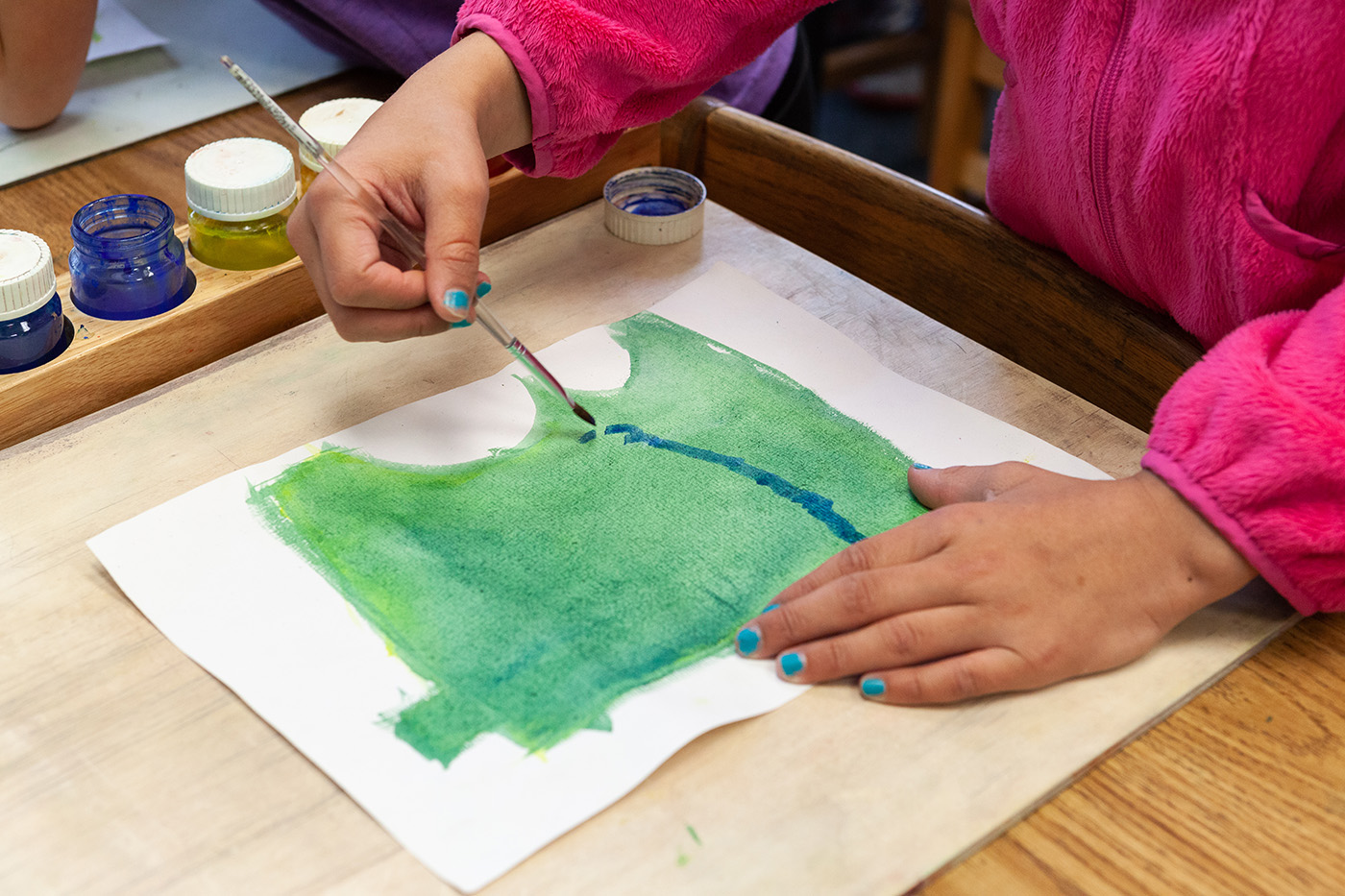 A fourth grade student uses watercolors to paint a map of Minnesota.