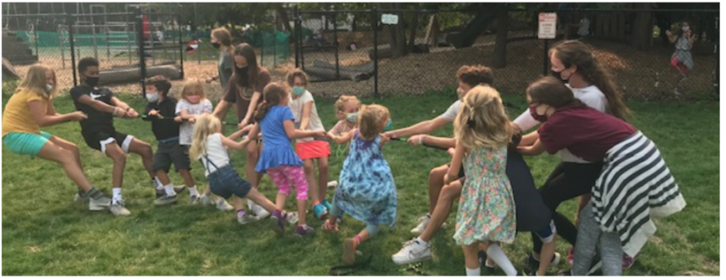 """First graders play """"tug of war"""" outdoors with their eighth grade buddies."""
