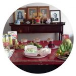 Lydia's family table, set with delicious food and photos of her ancestors.
