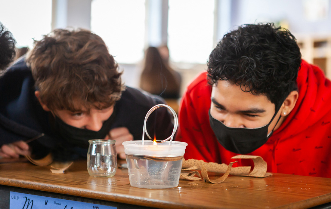 Two 8th grade students excitedly anticipate the result of their hand-built steam engine!