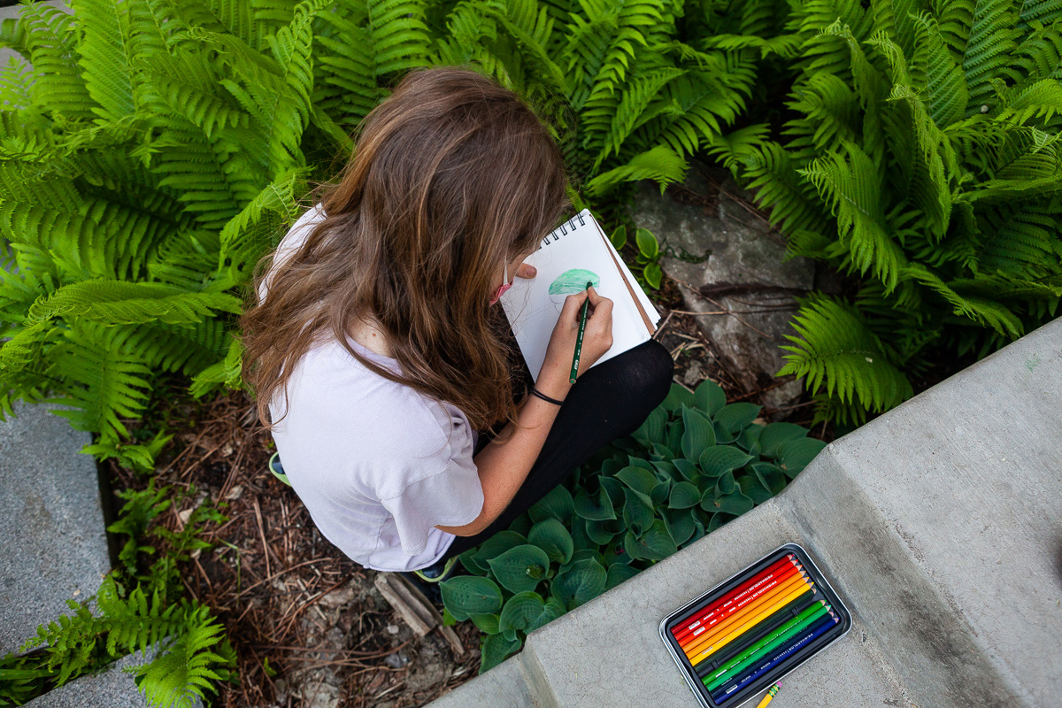 A CLWS 5th grade student works on a Botany assignment in the school's raingarden.